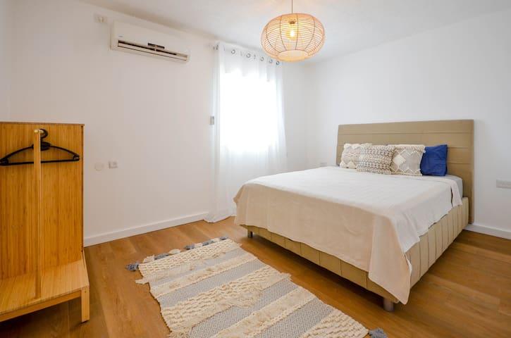 חדר שינה מאסטר ממוזג עם מיטה זוגית מפנקת.