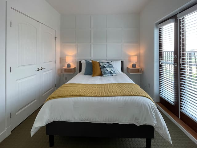 Bedroom 2 with Queen bed and Juliette balcony with view of Mission Hill winery