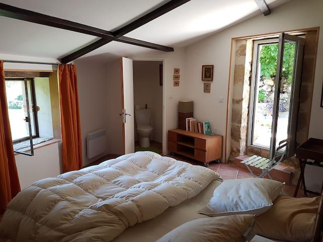 chambre avec accès direct sur patio, dotée d'un wc privatif, d'une bibliothèque et d'un dressing - vue sur le jardin et les collines environnantes.