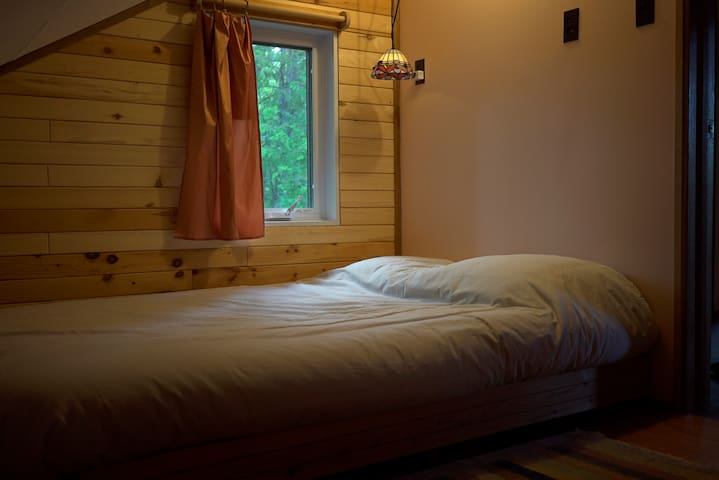 Corner bedroom with a double bed. This bed is medium-hard. Lovely Eastern window with morning light.