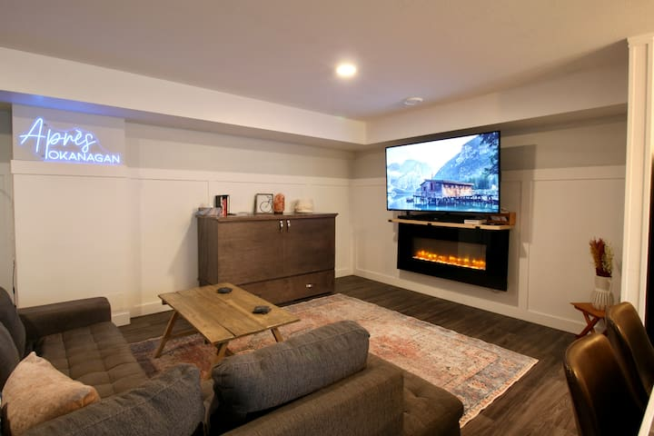 """65"""" Roku Smart Tv, comfy seating, and cabinet to the left of TV can be turned in to the second queen bed in the suite."""