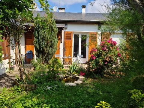 Maison chaleureuse avec bel extérieur fleuri.