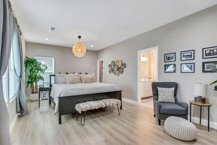 """Spacious Master bedroom with sitting area fireplace, 70"""" smart TV and en suite."""