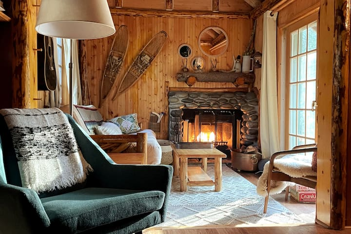 This quaint cabin, originally built in 1939, oozes vintage charm, from the knotty pine walled interiors to the cut log stairs and cozy fireplace