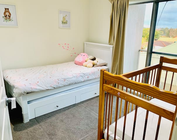 Kids bedroom with one single + pull out trundle bed and a cot
