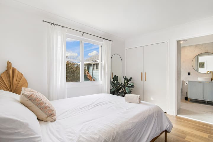 Bedroom & wardrobe area. The large windows lets in a huge amount of Eastern Facing daylight, but with black-out roller blind or sheer curtains the light levels are controlled by you. We are on a corner block so heaps of privacy even with blinds open