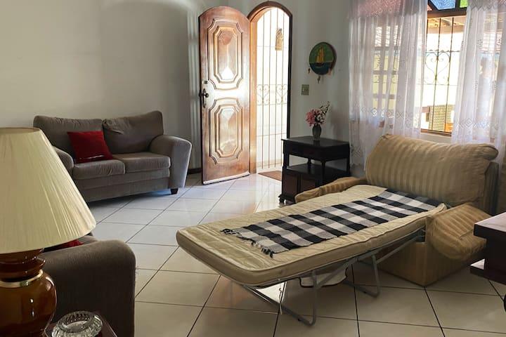 Sala com sofá cama solteiro, podendo adicionar um colchão de solteiro disponibilizado na casa.