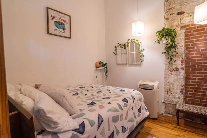 Bedroom: Plush queen casper mattress. Plants,. Exposed brick walls. Plants and small creative touches add a homey feel.