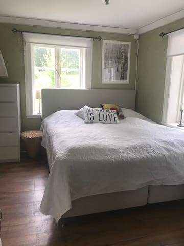 Sängkammare på nedervåningen med fungerande braskamin i rummet.