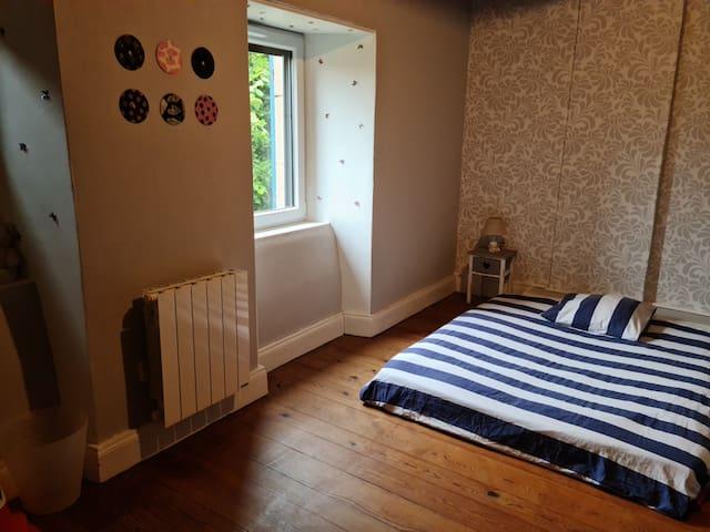 la seconde chambre avec un lit double au sol. une étagère est à la disposition pour nos invités. Cette chambre peut accueillir un lit bébé ou un matelas pneumatique 2 places sur demande.
