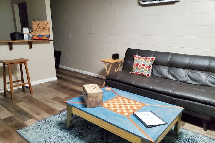 Very comfortable living room with game table, sofa that folds down to a bed, two chairs, bar dining area, and Smart TV with Amazon Fire Stick