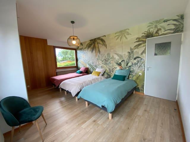 Trois lits simples et un espace de jeu pour cette chambre d'enfants.