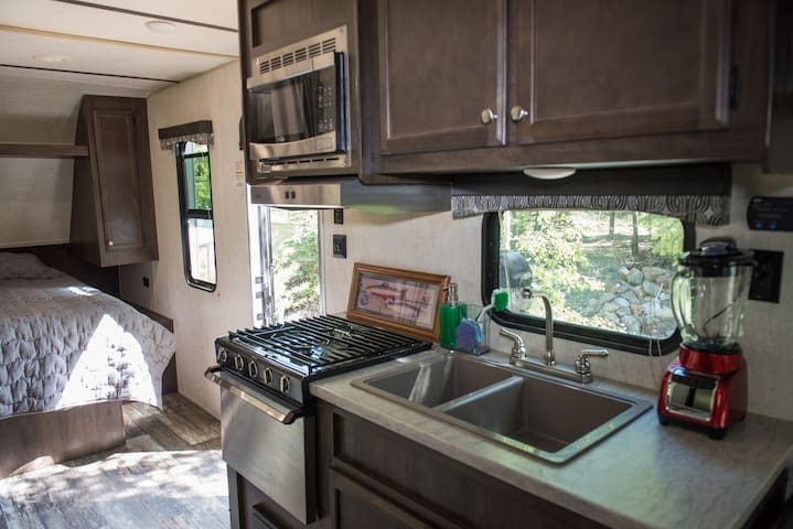 Queen Bed facing Creek, closet storage & Kitchen with stove, oven, microwave, double sink & all you need for comfortable cooking & dining