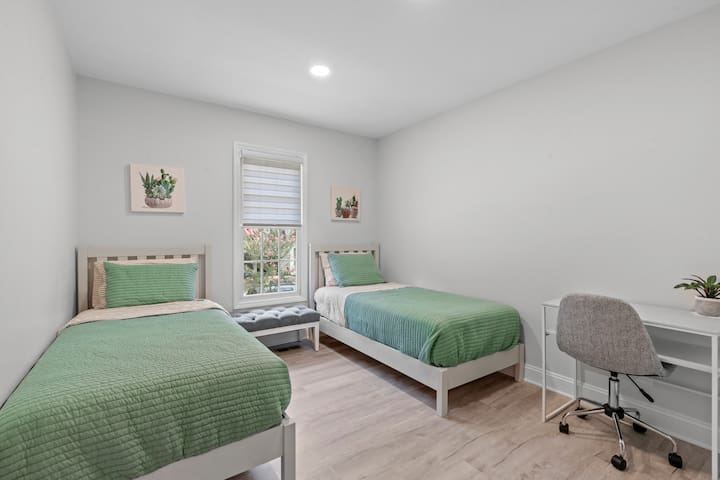 Two single beds and a desk with extension cord.