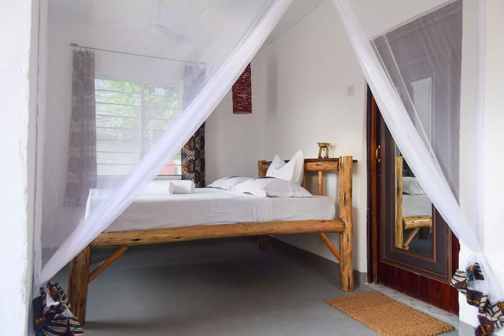 Welcome to KIMBIA House. Sleep your nights away in a cozy bedroom with mosquito net protection.