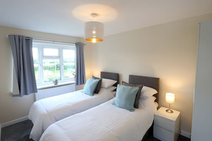 Second bedroom can be a twin or double room - with view over the cricket pitch and countryside beyond.