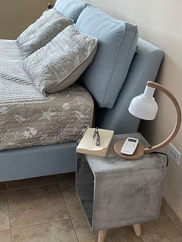 Nightstand and lamp besides bed.