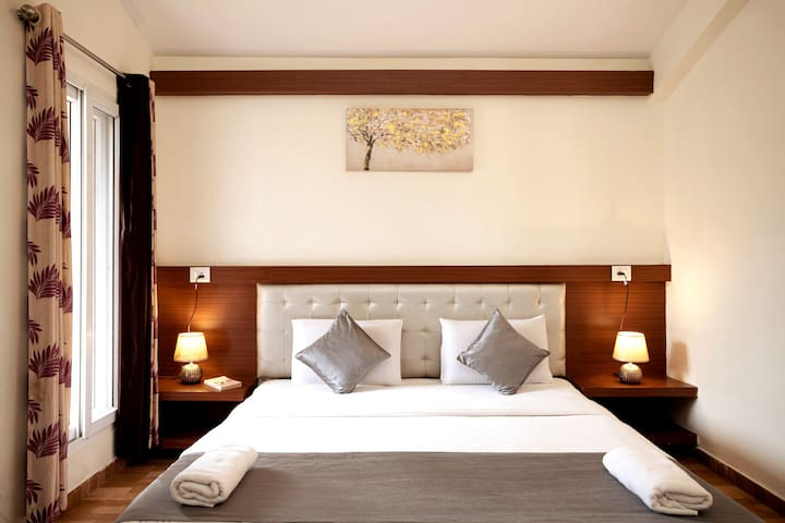 Modern King-Size Bed | Wingback Tufted Headboard | Bedside Tables | Wardrobe | Split Air Conditioning | Attached Balcony