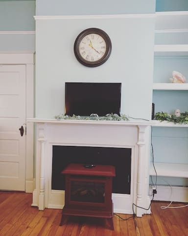 SMART flat screen TV with original fireplace wood mantel and electric fireplace for ambiance