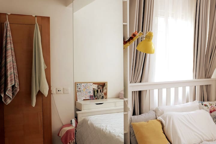 The bedroom has corner windows with sheer curtains to provide privacy, yet enough natural light. There are 2 big wardrobes - 1 for hanging your clothes, the other has shelve units. There will be sets of bedsheets provided of course.