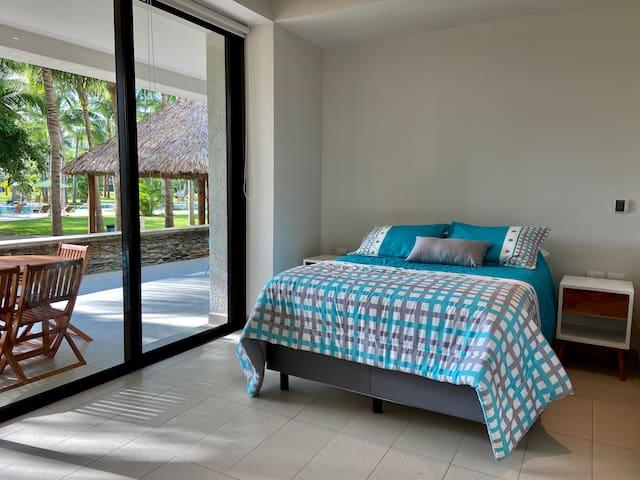 La habitación principal cuenta con cama Queen size, acceso a terraza y baño privado completo.