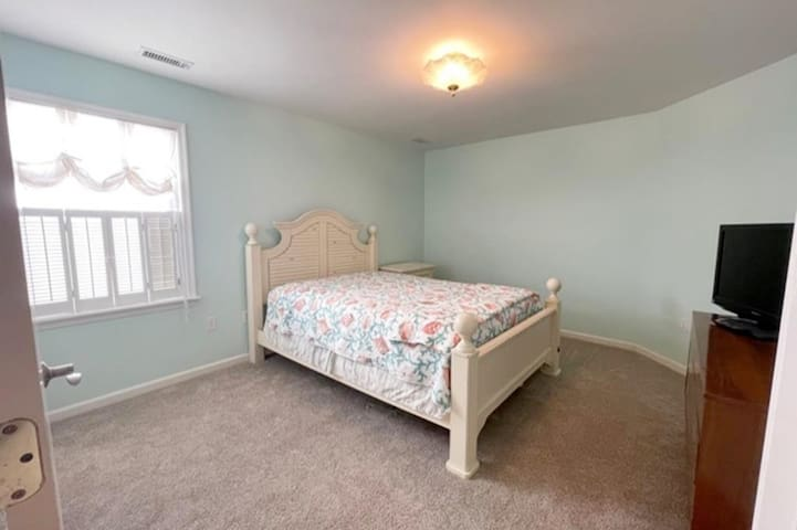 Primary Bedroom with plenty of space plus two closets, Roku TV, bedside table and dresser.