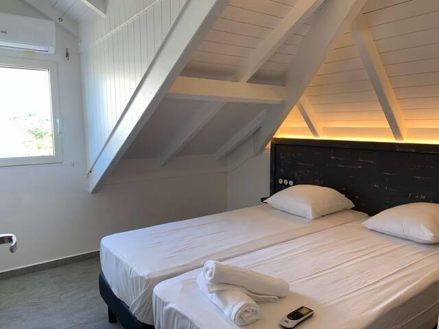 Chambre climatisée deux lits simples 90 x 200, prise USB et électrique, grande armoire de rangement