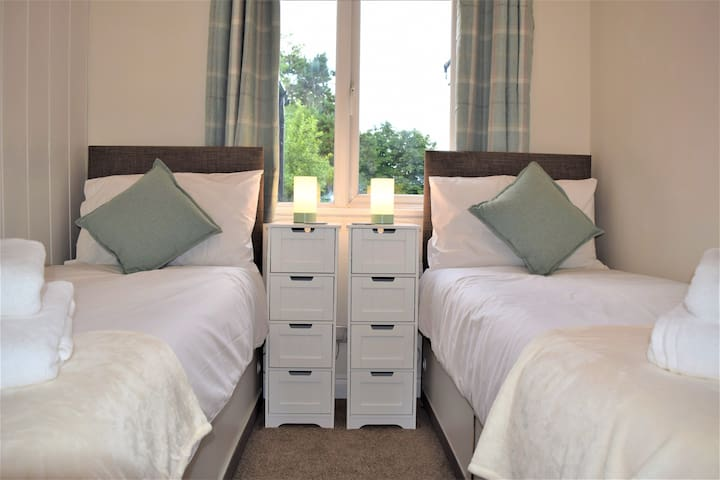 """Compact but functional bedroom 2 with twin beds (2'6"""" wide) that can be joined into a double if required. Hanging space for clothes and underbed storage with views out to the back garden."""