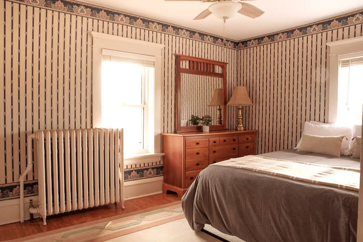 Bedroom 1 features bright windows, a Queen size memory foam mattress, and ceiling fan.