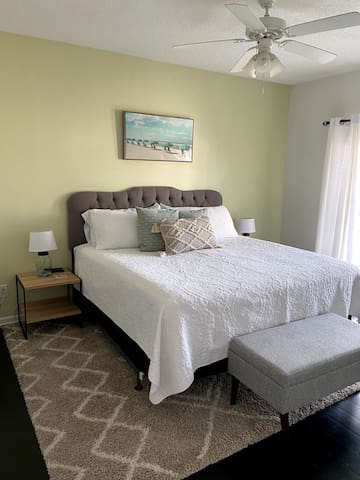 Welcome to the Mar-Gre Maison! Our primary bedroom features a king sized bed, ensuite bath, walk-in closet, & French doors to the screened-in patio.