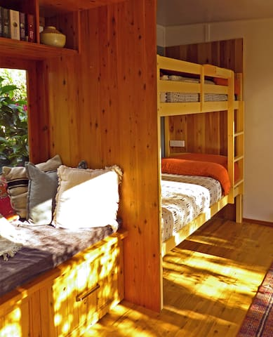 The cute sleeping nook and cosy window seat have views out to the deck and gardens.