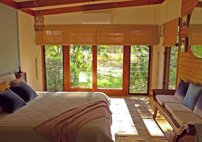 The main  bedroom with king size bed and views of the gardens and dam.