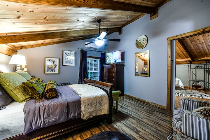 Master bedroom with smart Tv, 2 dressers, nightstand, luxurious linens, ceiling fan and it's own temp control mini split just for that space.