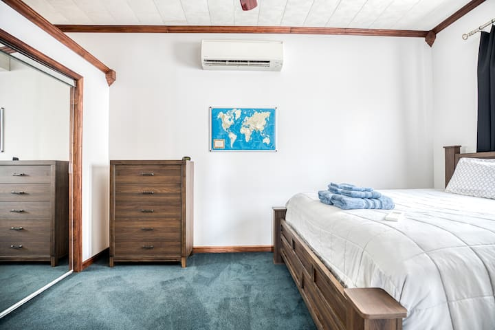 Bedroom has 10 foot high ceilings, king bed, 5 drawer dresser, full length mirror doors, luggage rack and wall A/C unit