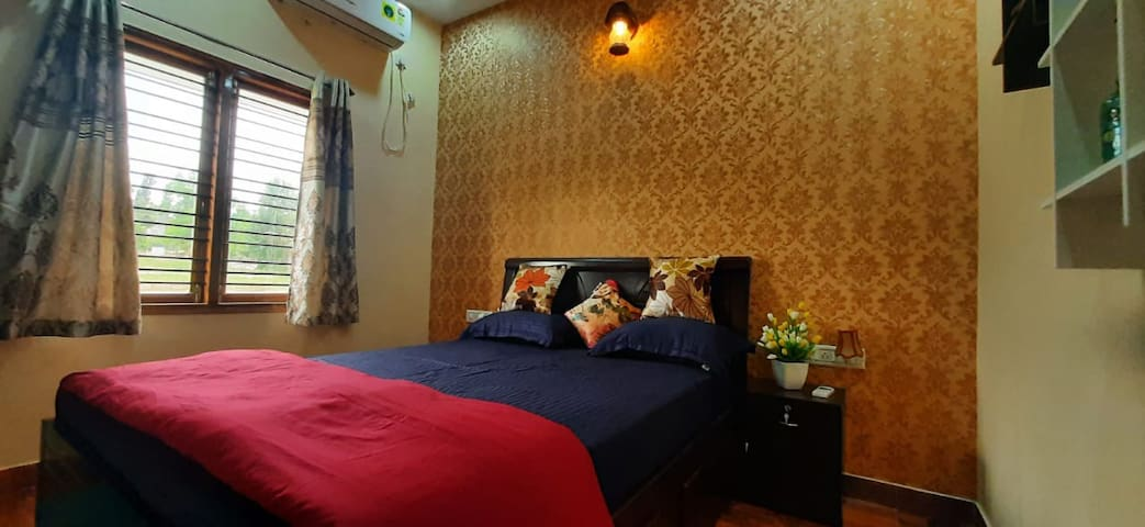 Air conditioned compact Ground floor bedroom with queen size bed and attached restroom.