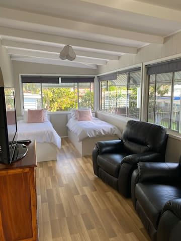 Spotlessly clean enclosed sunroom with 2 single beds and seperate TV and lounge