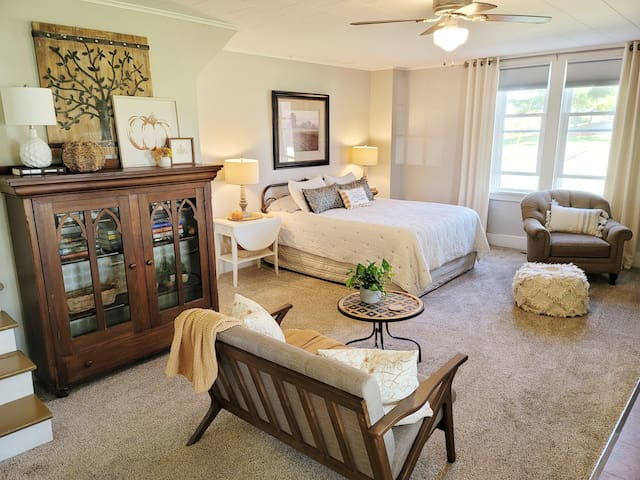 Main room is set up as a suite with Queen size bed and smart TV, Small love seat, closet and comfy chair for relaxing.