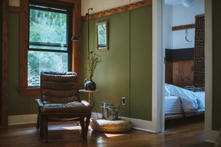 The Living Room — a cozy reading chair corner, stocked with guides for exploring the Catskills