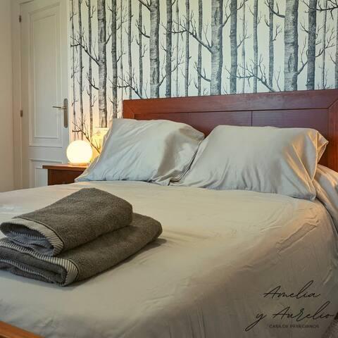 Habitación con cama de matrimonio y armario completo.