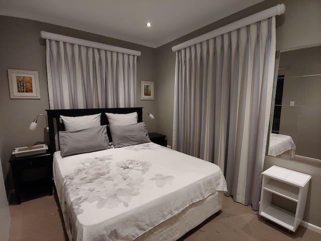 Main bedroom with queen size bed and en suite bathroom.
