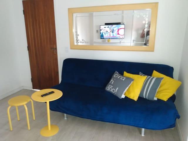 Sala de estar com confortável sofá cama e ar condicionado split.