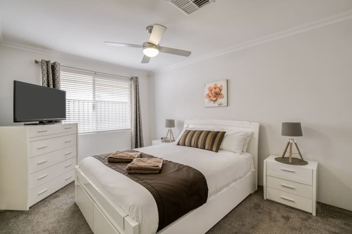The second bedroom comes with a comfortable queen-sized bed, side tables and TV.