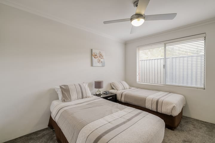 The fourth bedroom is fitted with two single beds, ceiling fan, a built-in robe and plenty of natural light.