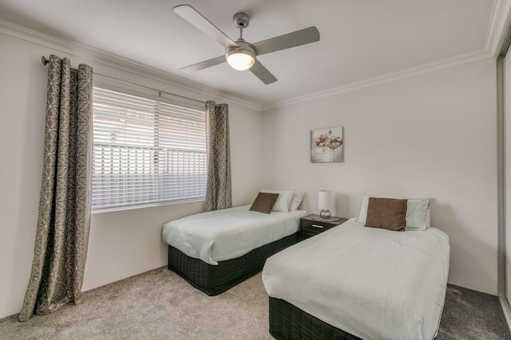 The third bedroom is fitted with two single beds, ceiling fan, black out blinds and plenty of natural light.