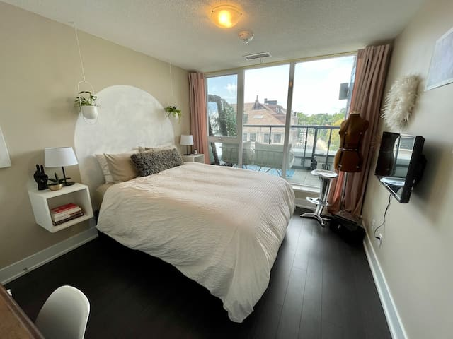 This bright bedroom features floor to ceiling windows.