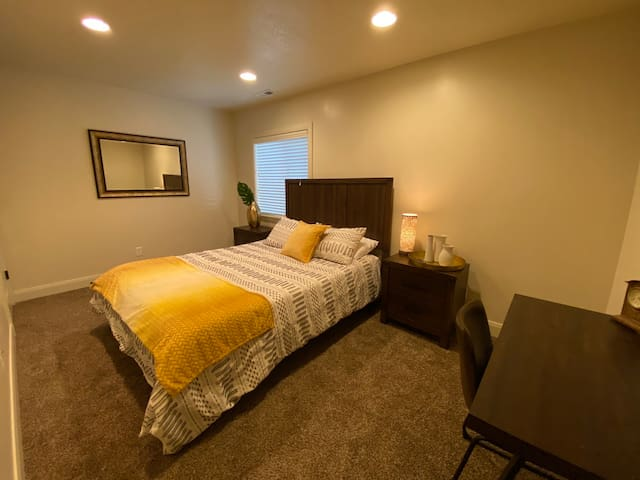 Queen bedroom with adjustable base, walk in closet, desk space, wall-mounted TV