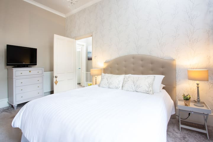 Master bedroom - bright and spacious, with King Size bed, generous en-suite with bath/shower, and adjoining dressing room