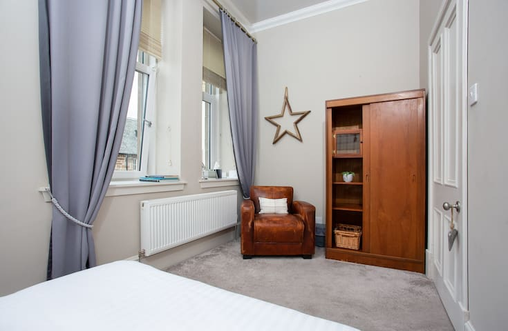 Bedroom 2 with double bed with comfy leather chair and wooden wardrobe