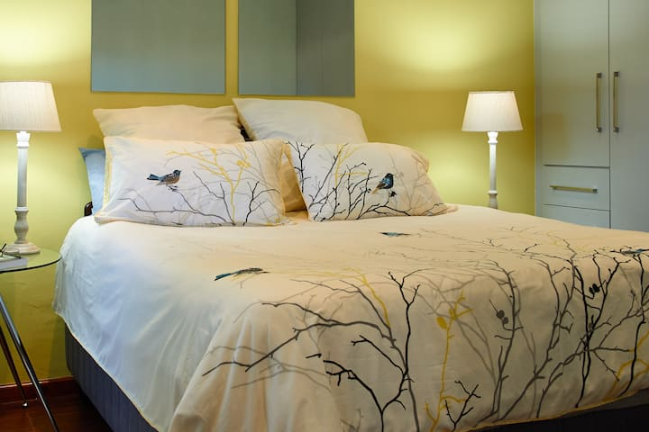 Master bedroom with queen size bed and built-in cupboards providing ample storage.