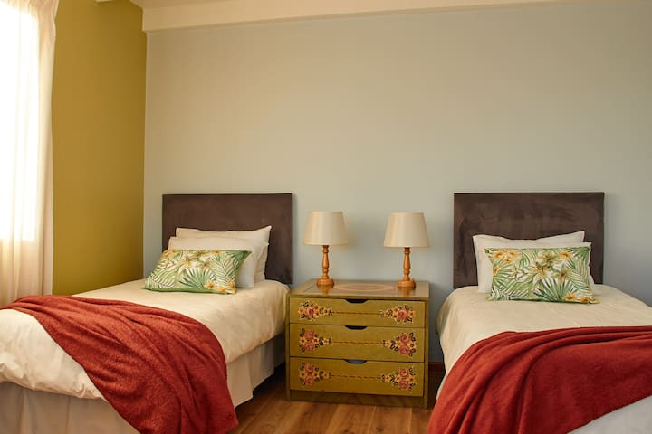 Second bedroom, generously sized with twin beds, a seating area and attached balcony with a view of Table Mountain.
